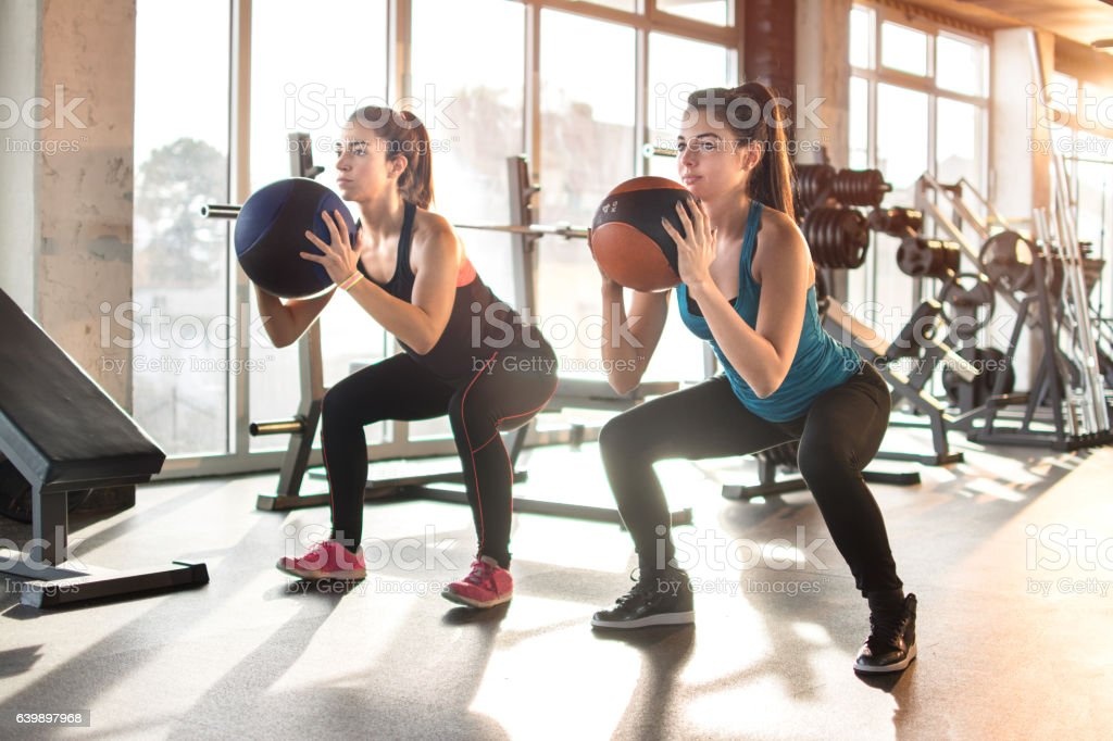 Attractive young women exercising with pilates ball at gym. stock photo
