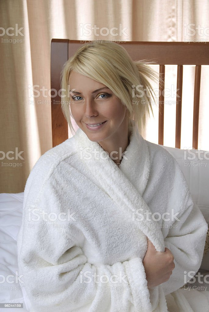 Attractive young women in bed wearing robe looking at you royalty-free stock photo