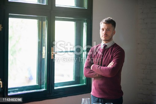 Portrait of an handsome, elegant young businessman standing at the restaurant.