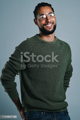 Studio portrait of a handsome and stylish young man posing against a grey background