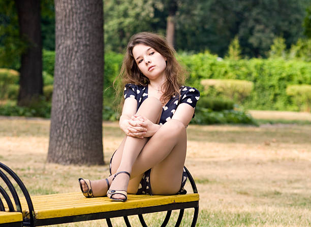 attractiver  young woman crossed her legs on park bench - mini dress stock photos and pictures