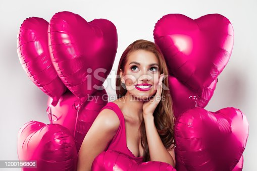 Attractiveyoung woman with pink heart balloons on white background