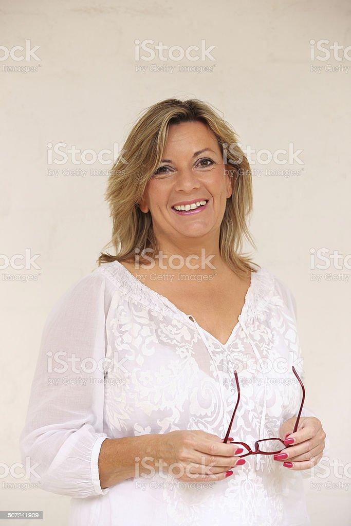 Attraktive white dressed mature blonde holding glasses portrait royalty-free stock photo