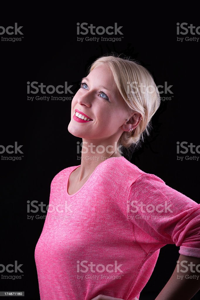 Attraktive young blond woman on black looking up royalty-free stock photo
