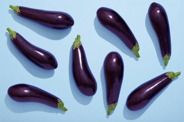 aubergines on blue background, eggplant flat lay - melanzane foto e immagini stock