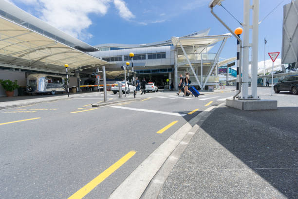 Auckland Airport people arriving to depart AUCKLAND, NEW ZEALAND - NOVEMBER 23, 2017 People including young couple pulling suit cases crossing road towards entranance to international airport terminal. depart stock pictures, royalty-free photos & images