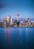 Auckland's CBD seen from across the water at dawn, with the Sky Tower in the centre of the image.