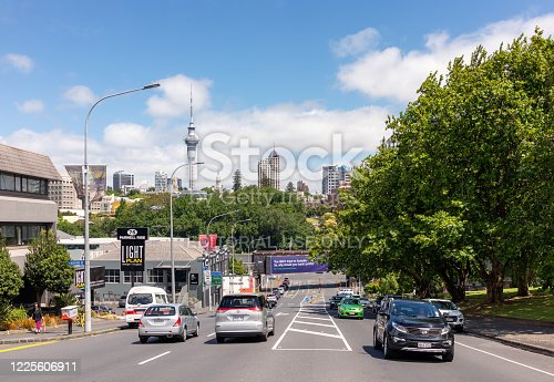 Auckland, New Zealand - Cars on a street in Parnell, Auckland, with the Sky Tower and the city's skyline on the horizon.