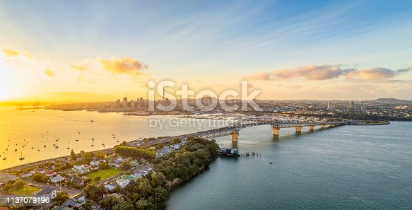 A panoramic image from above of Auckland, with the Sky Tower and CBD visible across Waitemata Harbor and the Auckland Harbour Bridge.
