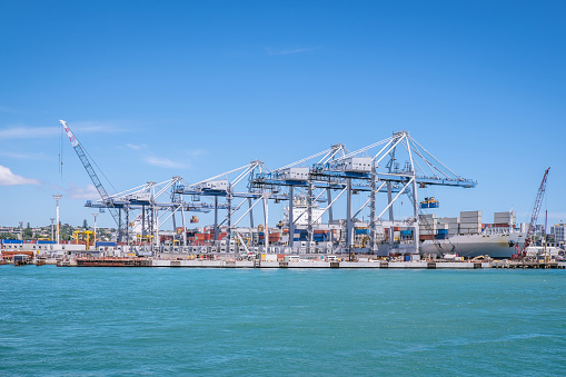 Auckland port with shipping containers, cranes and ship providing transportation for imports and exports in New Zealand, NZ