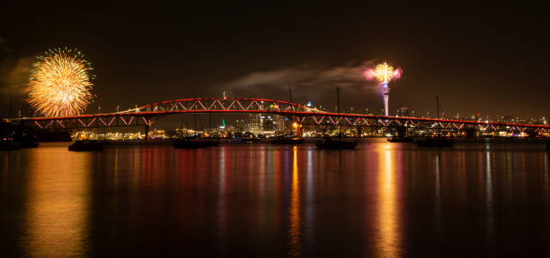 Auckland Sky Tower fireworks for New Year celebration with Harbor bridge illuminated in red Auckland Sky Tower fireworks for New Year celebration with Harbor bridge illuminated in red dazzled stock pictures, royalty-free photos & images