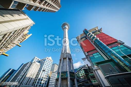 Sky Tower in Downtown Auckland surrounded with skyscrapers from below against blue summer sky. Ultra Wide Angle Shot. Auckland, New Zealand, Oceania.