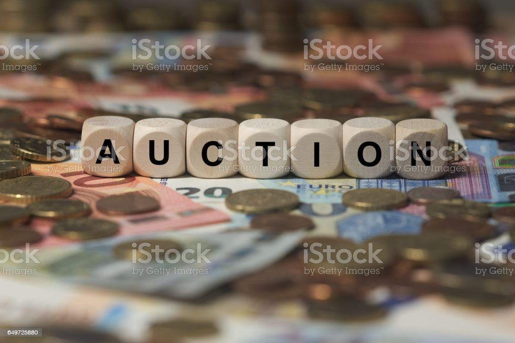 auction - cube with letters, money sector terms - sign with wooden cubes stock photo