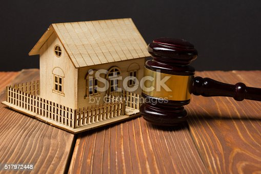 istock Auction. Law. Miniature House on wooden table and Court Gavel 517972448