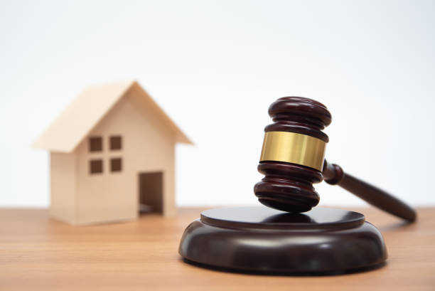 Auction or law concept. Miniature House on wooden table and judge gavel. stock photo