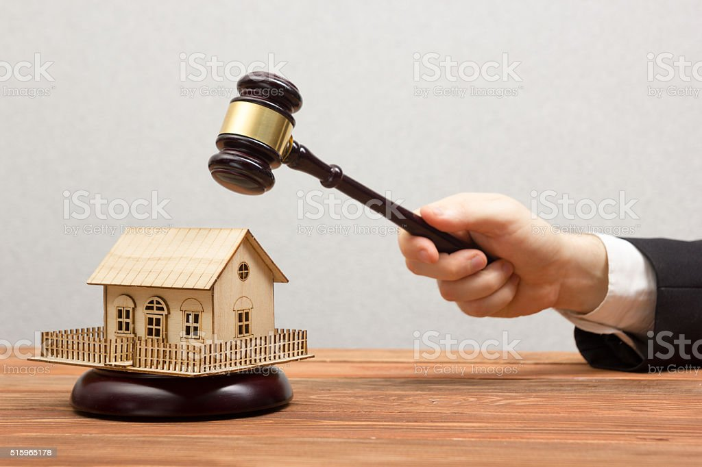 Auction, Real Estate concept. Hand with judge gavel and house stock photo