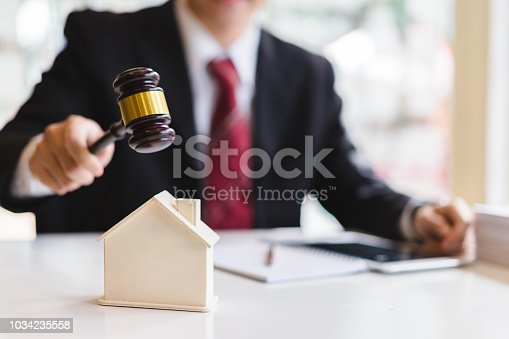 istock Auctioneer knocking down a model house with his gavel, Property sale auction concept 1034235558