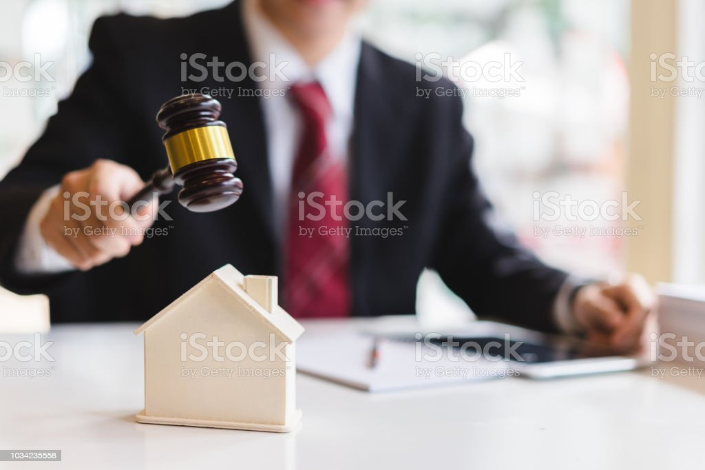 Auctioneer knocking down a model house with his gavel, Property sale auction concept stock photo
