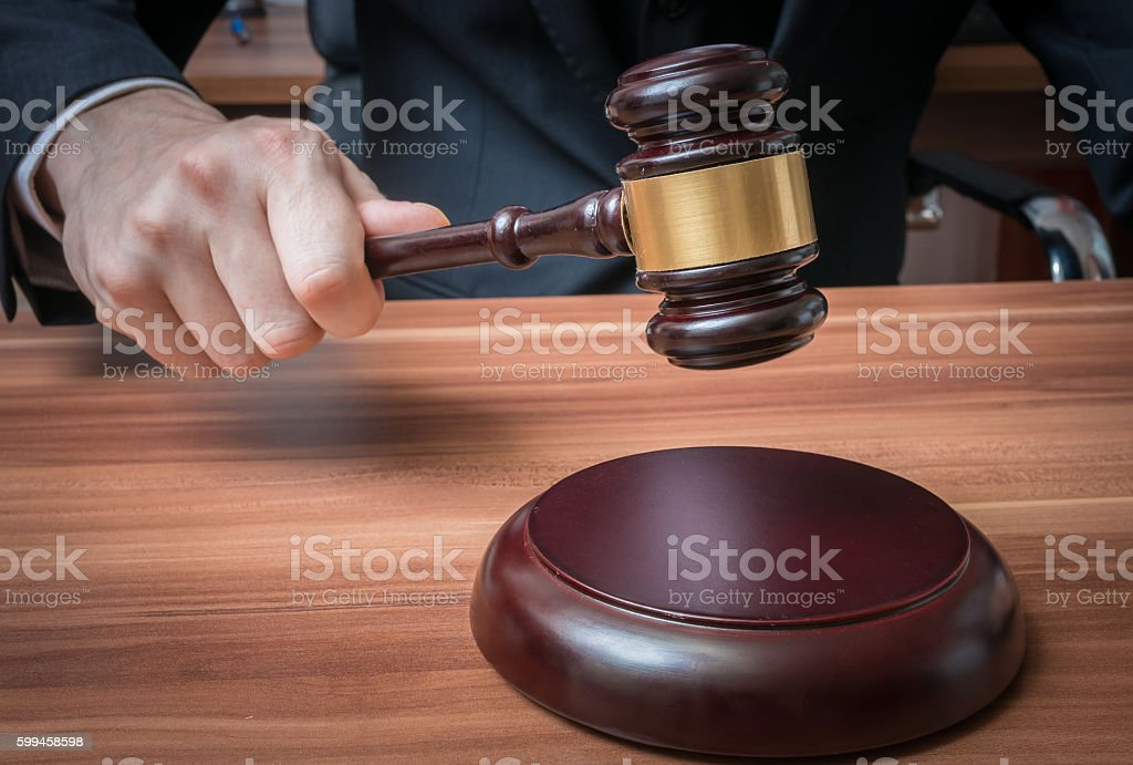 Auctioneer or judge is hitting with wooden gavel. stock photo