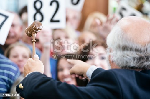 1050485096 istock photo Auctioneer with Large Crowd of Buyers 478631928