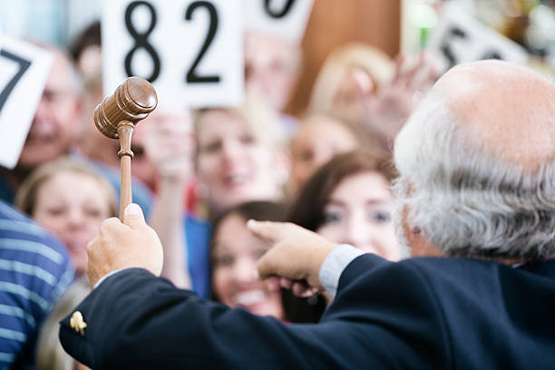 Auctioneer with Large Crowd of Buyers stock photo