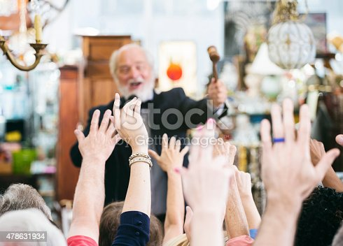 1050485096 istock photo Auctioneer with Large Crowd of Buyers 478631934