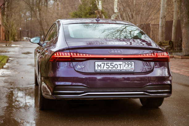 Audi A7 Sportback Ultra Nova GT 1 of 111 A purple-colored premium car stands in the street  back side view stock photo