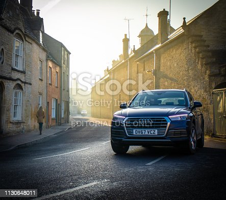 15th February, 2019 - Audi Q7 4x4 car diving through the Cotswold town of Cirencester on a misty morning commute