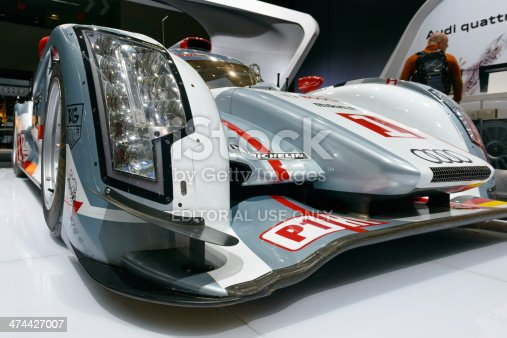 Brussels, Belgium - January 14, 2014: Close up of the Audi R18 e-tron Qauttro  Le Mans Prototype (LMP) racing car. Racing drivers Tom Kristensen, Alan McNish and Loic Duval won the 2013 edition of the 24 hours of Le Mans in this car. A man is standing behind the car.