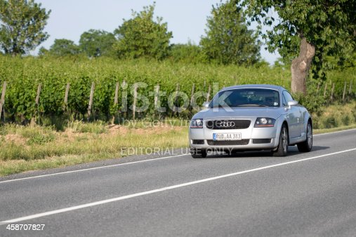 Eltville, Germany - June 3, 2011: A woman in an accelerating silver-metallic Audi TT coupe on a country-road in the Rheingau near Eltville, Germany. Audi TT is a two-door sports car produced by the German car manufacturer Audi. It was introduced in 1998. Audi AG is a German manufacturer of automobiles, the company is headquartered in Ingolstadt, Germany, and is a wholly owned subsidiary of Volkswagen AG.