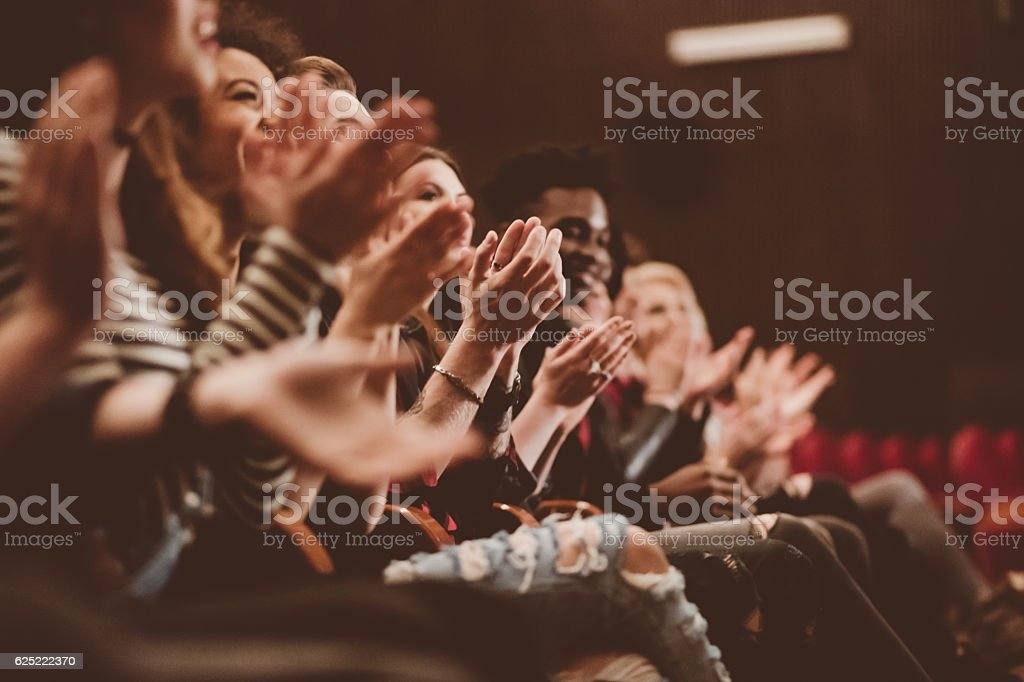 Audience applauding in the theater Group of people clapping hands in the theater, close up of hands. Dark tone. 20-29 Years Stock Photo