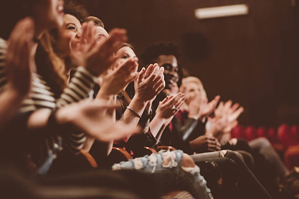 Audience applauding in the theater Group of people clapping hands in the theater, close up of hands. Dark tone. event stock pictures, royalty-free photos & images