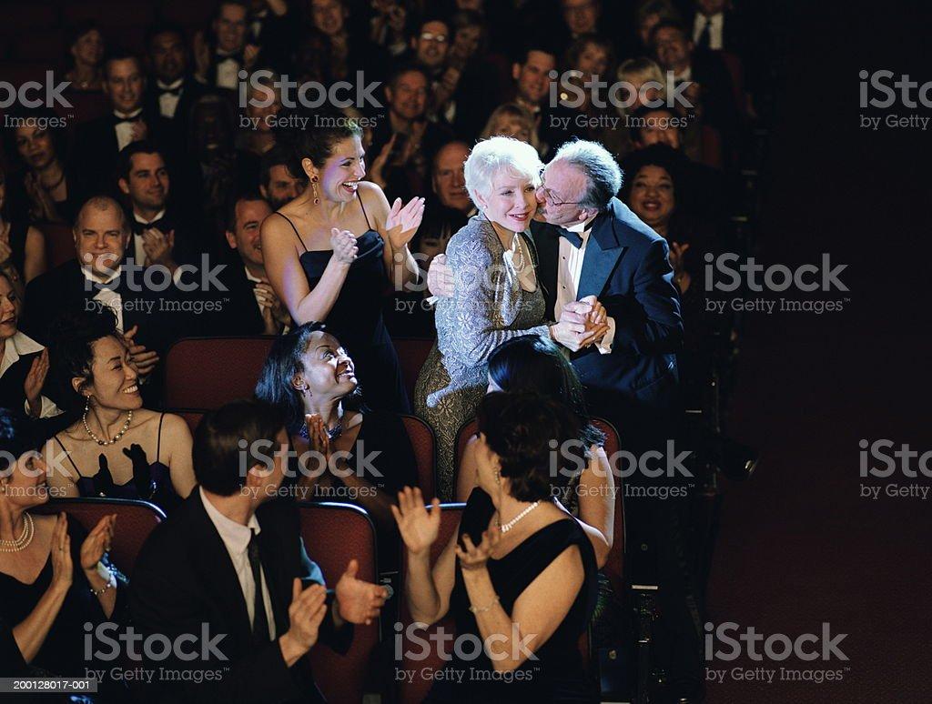 Audience applauding mature woman, husband kissing cheek stock photo