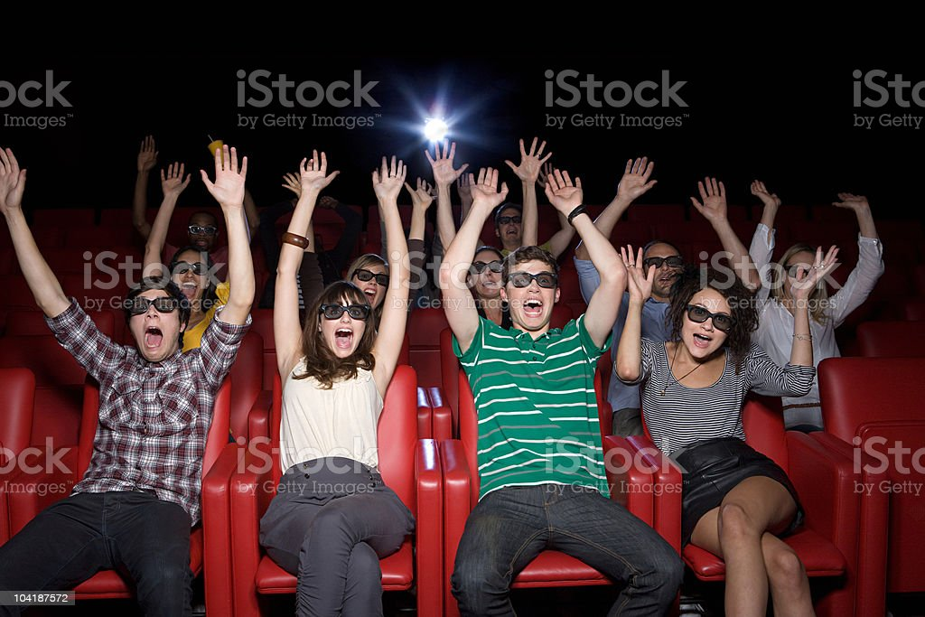 Audience at 3d movie with arms up royalty-free stock photo