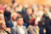 Defocused photo of an audience at a conference event.