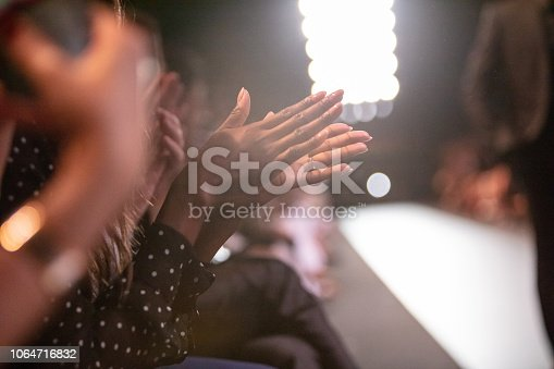 Close-up of audience applauding at fashion show