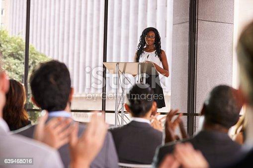 istock Audience at seminar applauding young black woman at lectern 639468016