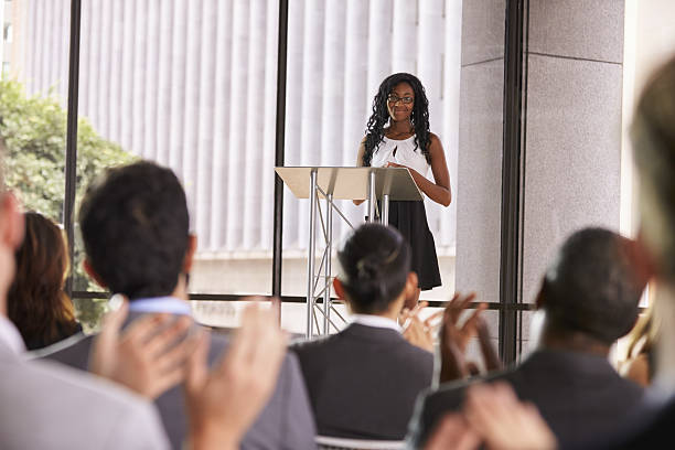 audience at seminar applauding young black woman at lectern - oratore pubblico foto e immagini stock