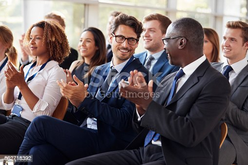 862718922 istock photo Audience clapping at business seminar, looking at each other 862718392