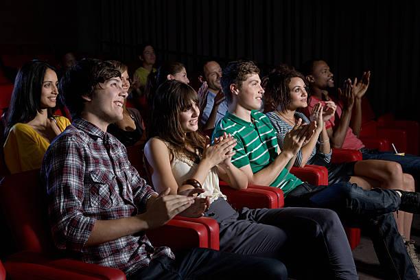 publikum klatschen in movie theater - jugendfilm stock-fotos und bilder