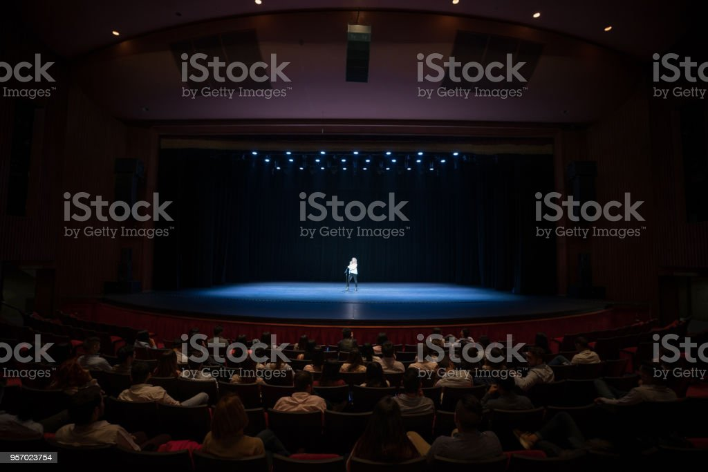 Audience enjoying a singing performance on stage stock photo
