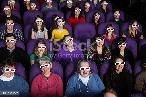 An audience wearing 3D glasses in a darkened movie theater.