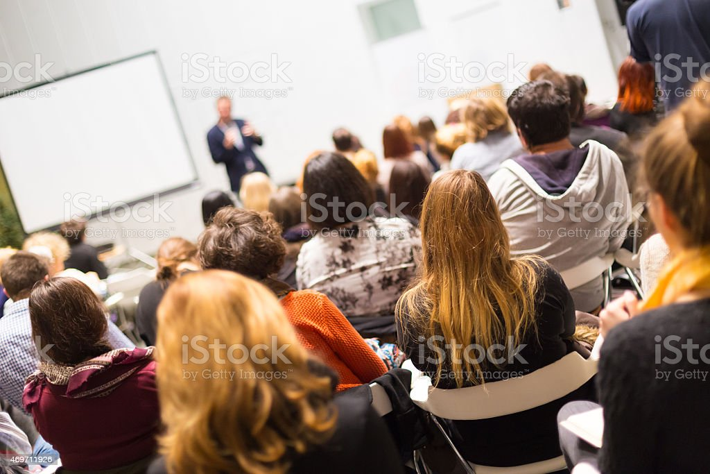 Audience in the lecture hall. Speaker Giving a Talk at Business Meeting. Audience in the conference hall. Business and Entrepreneurship. Copy space on white board. 2015 Stock Photo