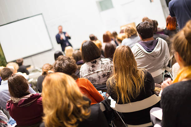 Audience in the lecture hall. Speaker Giving a Talk at Business Meeting. Audience in the conference hall. Business and Entrepreneurship. Copy space on white board. lecture hall stock pictures, royalty-free photos & images
