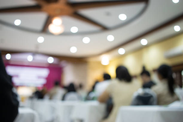 Audience listening speaker speech in conference hall or seminar room with blur light people background. Seminar is form of academic instruction, offered by commercial or professional organization. stock photo