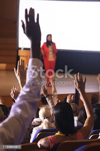 1133973551 istock photo Audience raising hand for asking question in the auditorium 1133855922