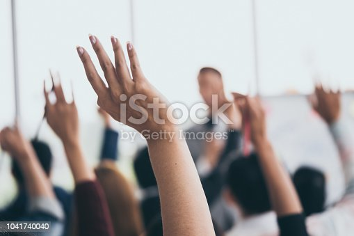 istock Audience raising hands up while businessman is speaking in training at the office. 1041740040