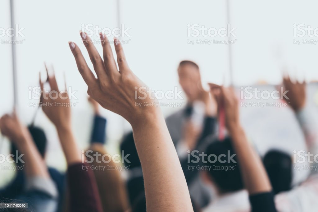 Audience raising hands up while businessman is speaking in training at the office. stock photo
