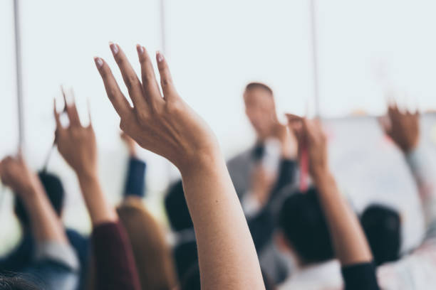 audience raising hands up while businessman is speaking in training at the office. - train stock photos and pictures