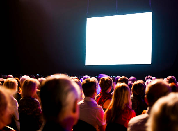 audience watching a bright blank screen - projection screen stock photos and pictures